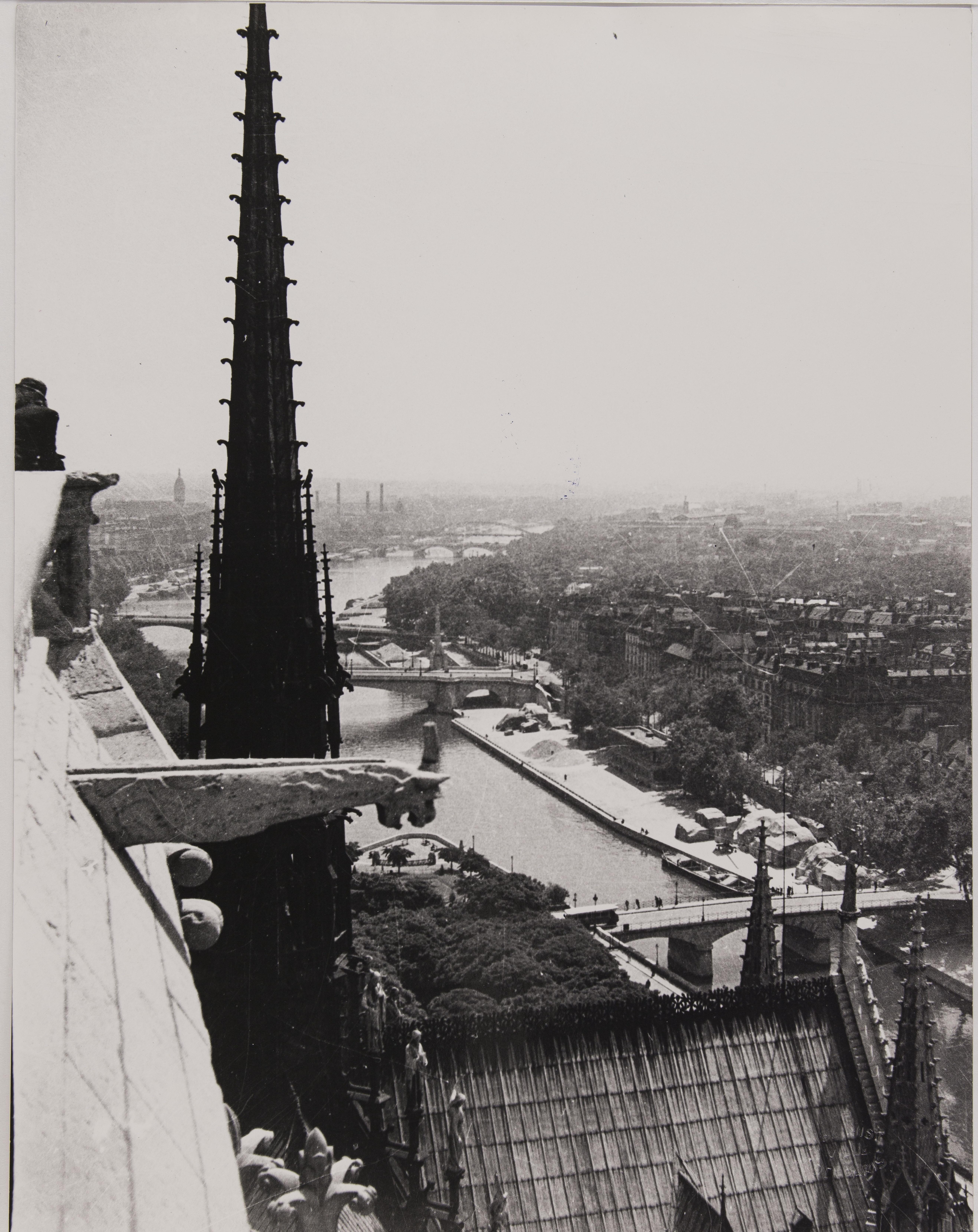Flèche, toît et gargouille de Notre-Dame de Paris avec panorama sur la Seine, vers l'est, une photographie de Jean Roubier, avant 1938, tirage gélatino-argentique sur papier baryté ; 23 x 18 cm. 4-ENA-00042-0057, Ville de Paris / BHVP, https://bibliotheques-specialisees.paris.fr/ark:/73873/pf0001880006, Cliquer sur la photo pour voir l'original et ses références